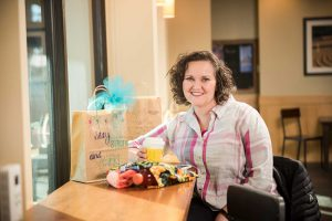 Shay Jones seated at counter with care package